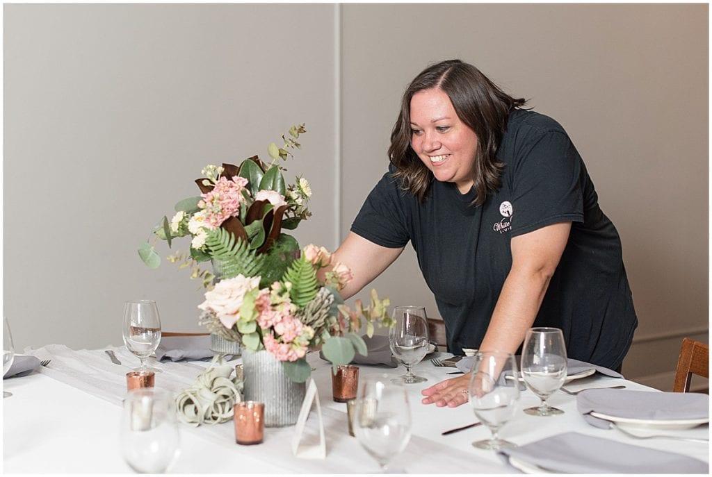 Wedding Coordinator placing centerpieces.