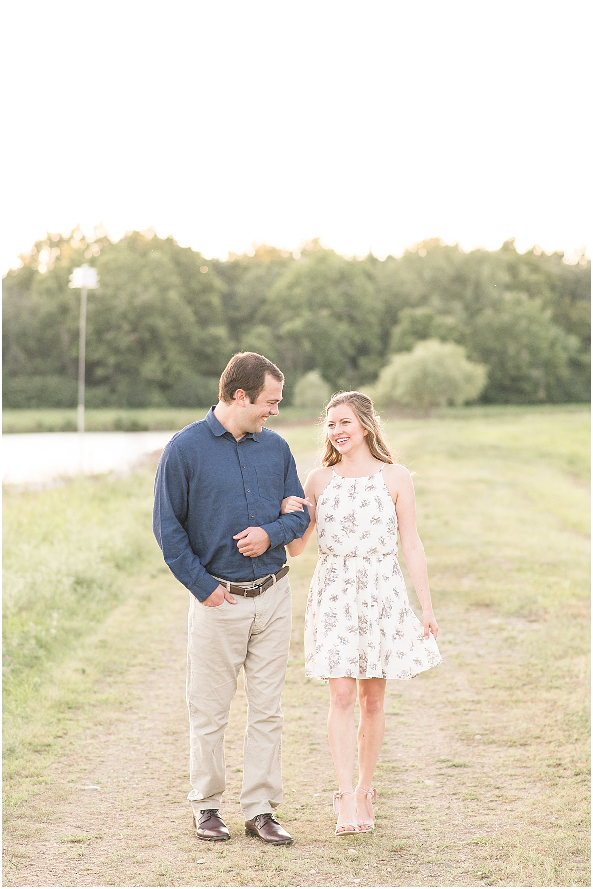Couple walking by water during Lakefront engagement photos in Lafayette, Indiana