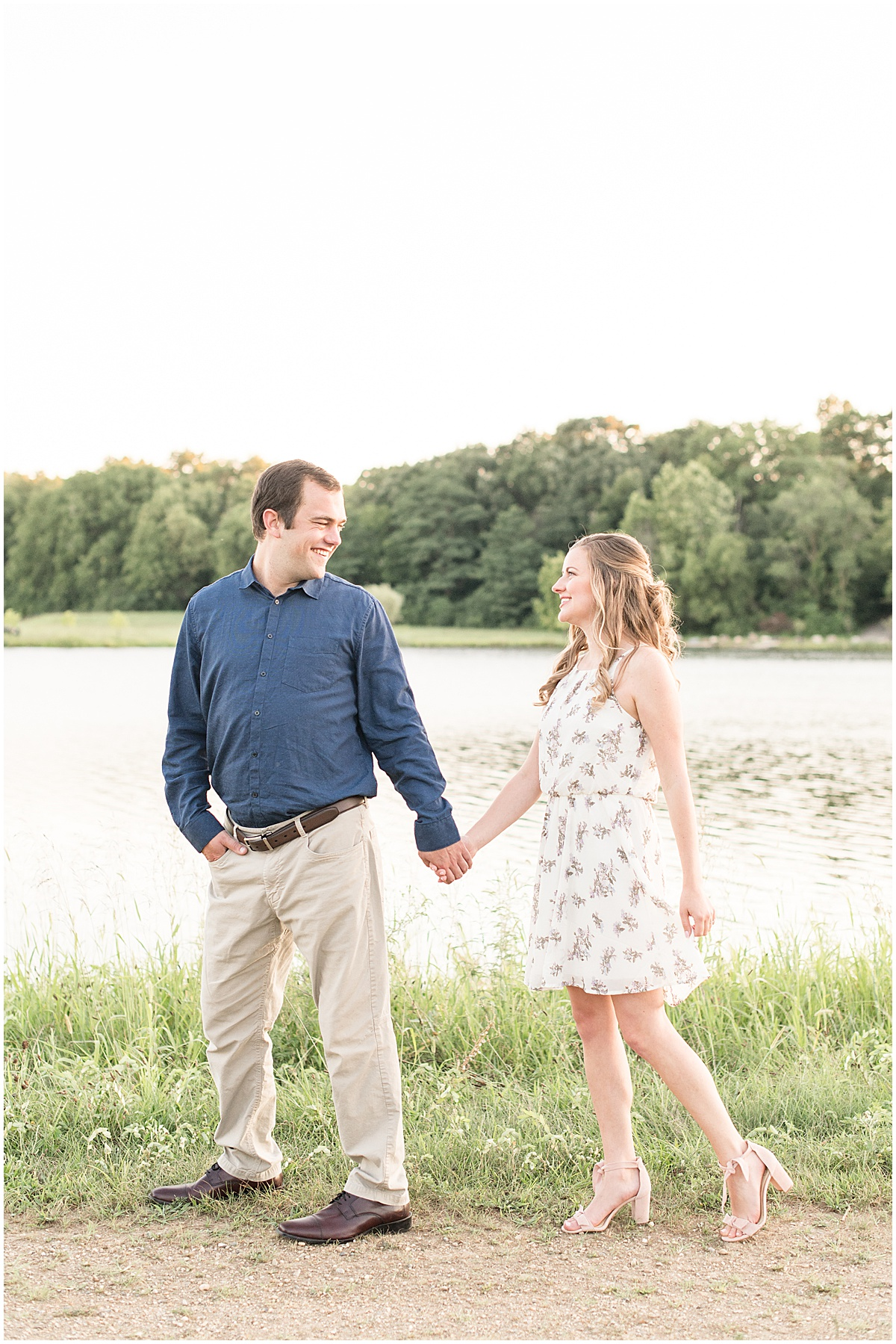 Engaged couple walking by water in Lakefront engagement photos in Lafayette, Indiana