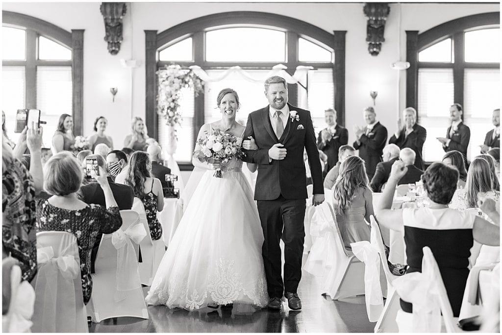 Walking down the aisle at Spohn Ballroom wedding in Goshen, Indiana