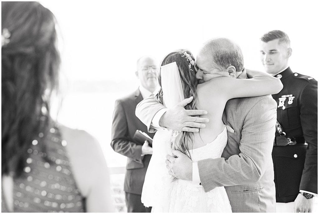 Father of the bride hugs bride during wedding at the Lighthouse Restaurant in Cedar Lake, Indiana
