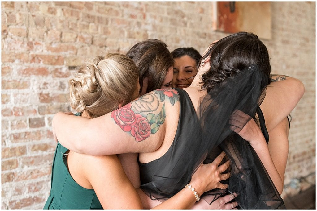 Bride and bridesmaids hug before eMbers Venue wedding