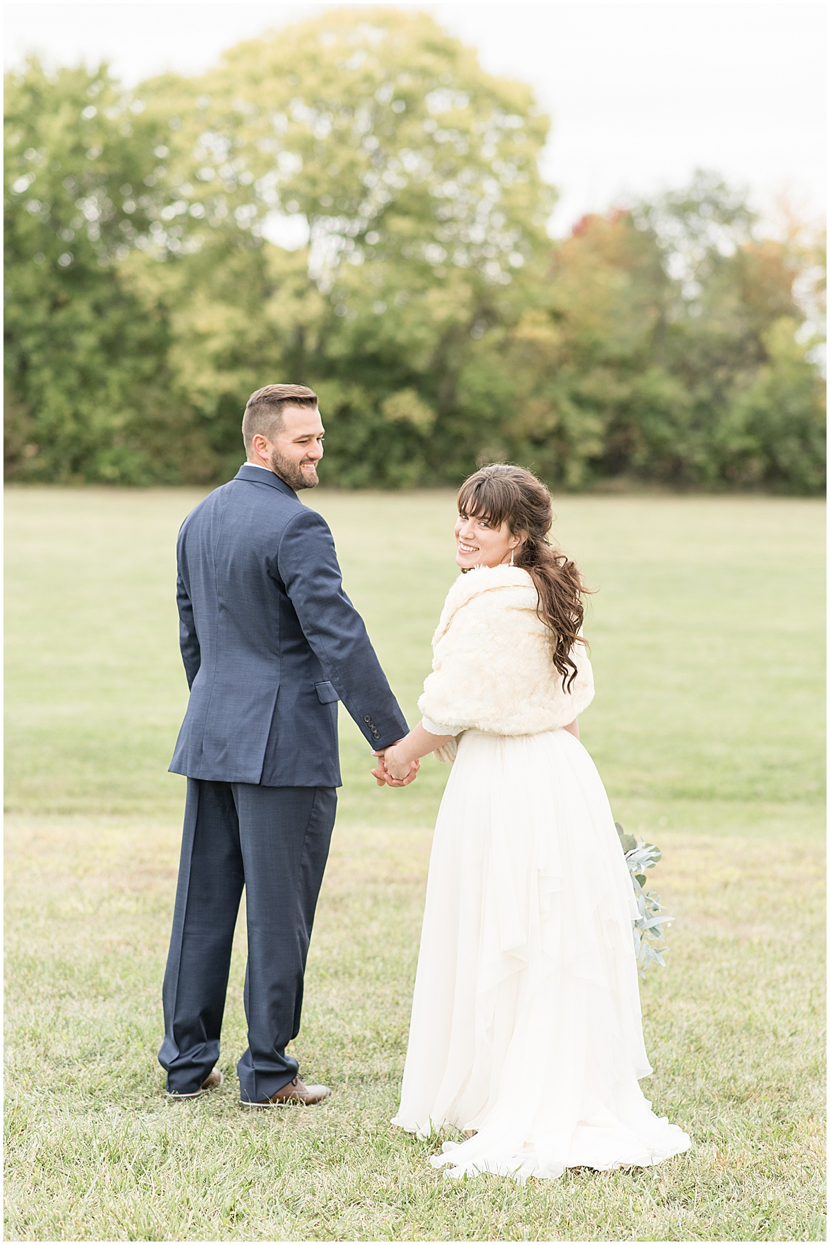 Bride and groom hold hands after fall wedding in Lafayette, Indiana