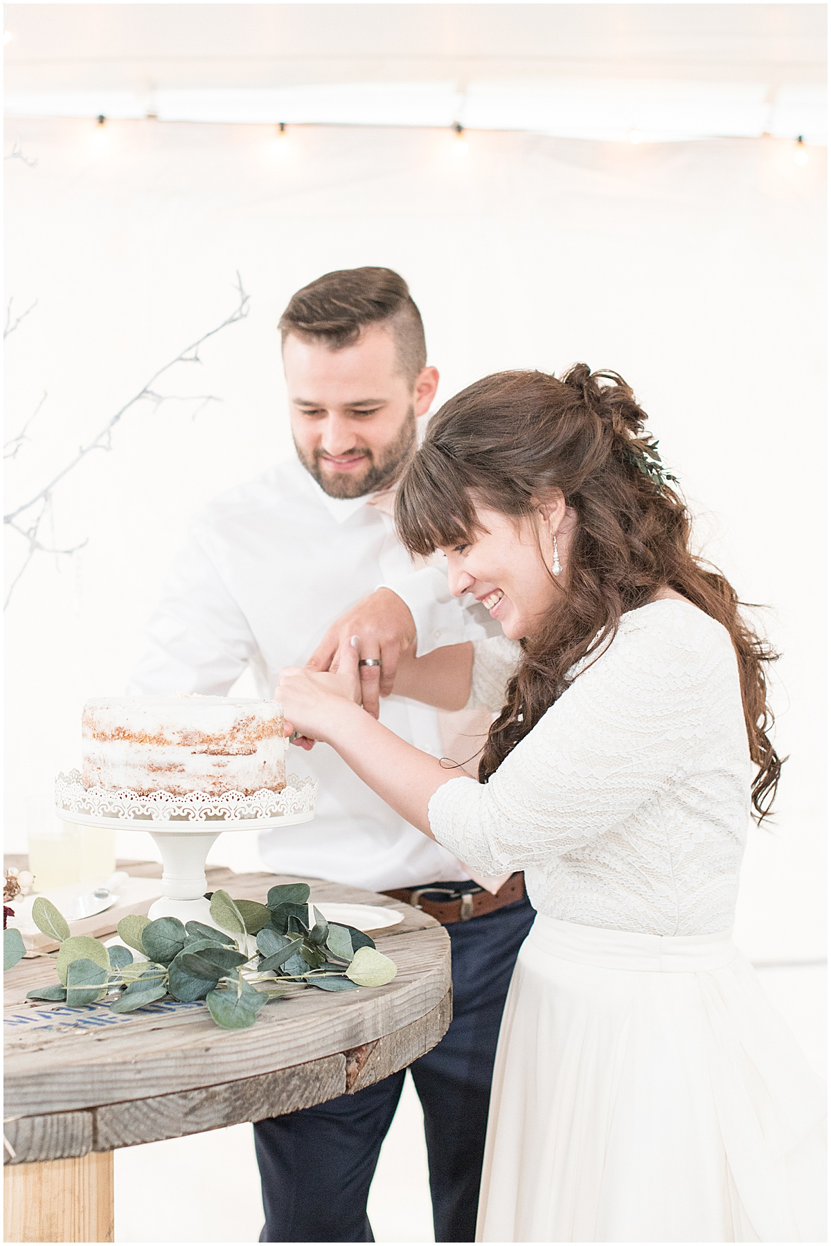 Bride and groom cut cake during reception in Lafayette, Indiana