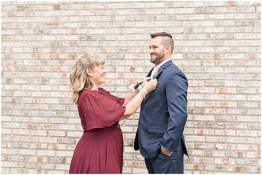 Mother of the groom helps him prepare for his wedding ceremony