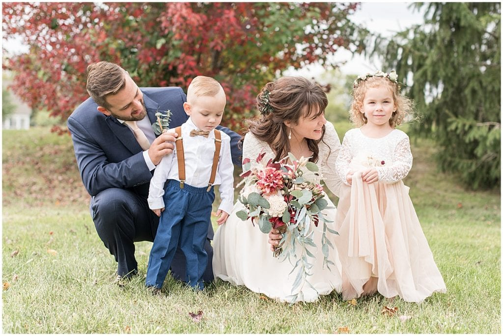 Bride and groom spend time with flower girl and ring bearer before wedding ceremony
