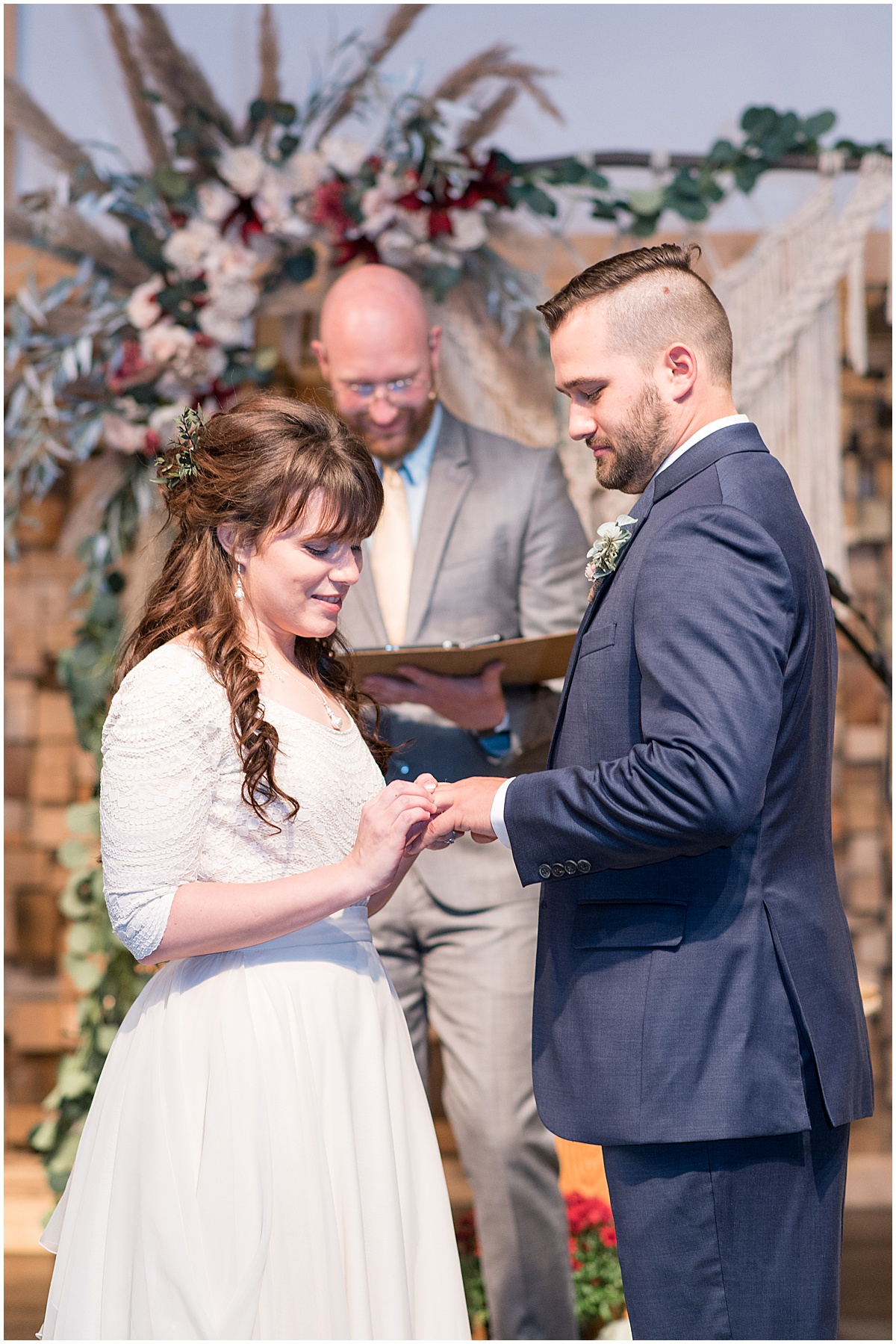 Bride puts ring on grooms finger during wedding at Innovation Church in Lafayette, Indiana