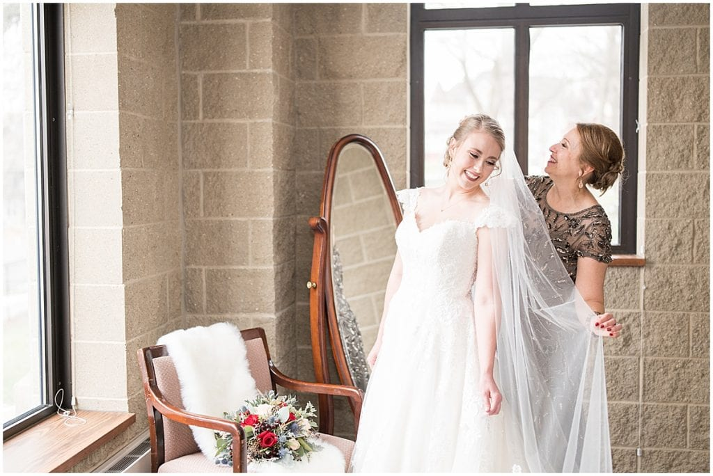 Mother of the bride helping the bride get ready for her winter wedding
