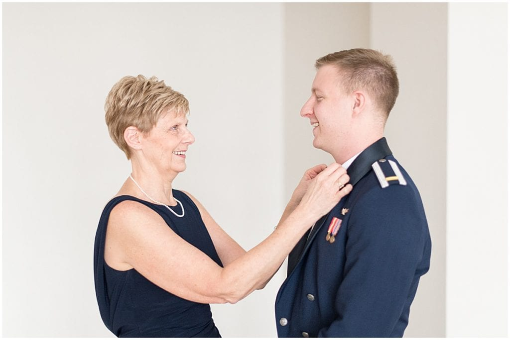 Mother of the groom helping groom get ready for winter wedding in Lafayette, Indiana
