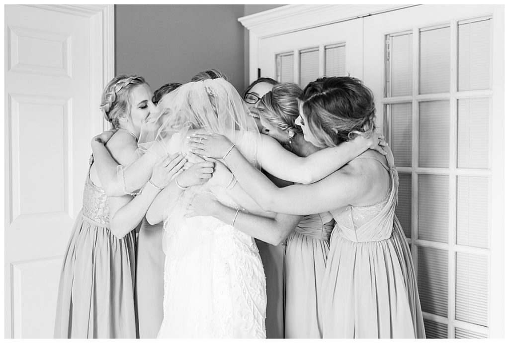 Bridesmaids embrace bride before her wedding in Lafayette, Indiana