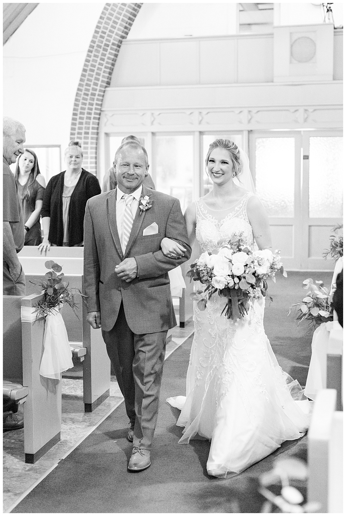 Bride walking down the aisle during wedding ceremony at Chalmers Community Church in Chalmers, Indiana
