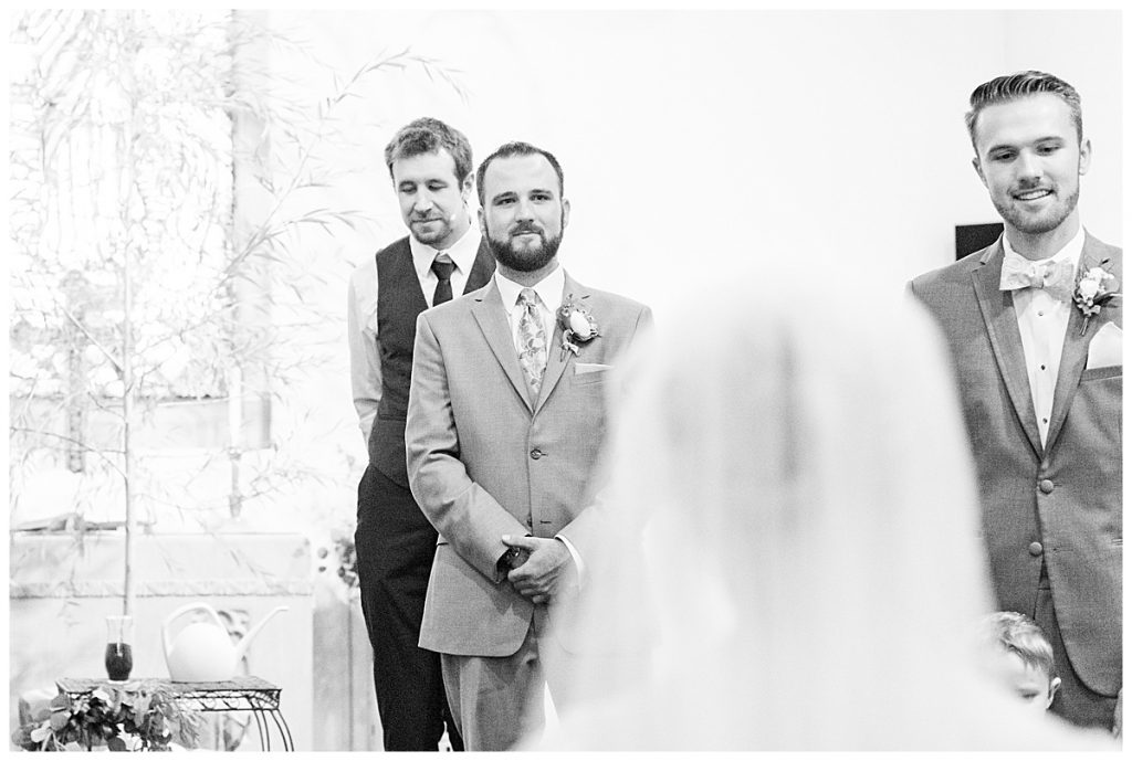 Grooms reaction to bride at wedding ceremony at Chalmers Community Church in Chalmers, Indiana