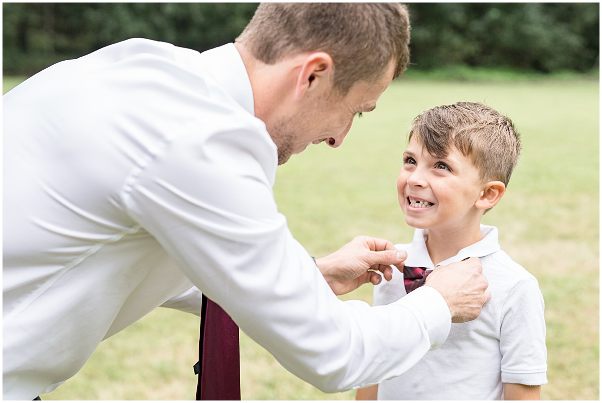 Groom fixing bowties before Wildcat Conservation Club wedding in Mulberry, Indiana